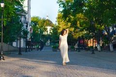 Mujer hermosa joven, oscuro-cabelludo, caminando abajo de la calle en el centro de ciudad en un día soleado, en un vestido blanco Foto de archivo libre de regalías