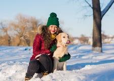 Mujer hermosa joven que abraza el perro del golden retriever Imagenes de archivo