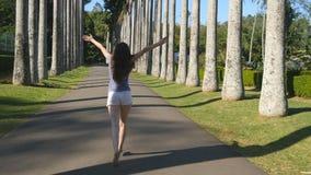 Mujer hermosa joven que activa y que hace girar a lo largo de parkland exótico y que se divierte La muchacha feliz está corriendo Imagenes de archivo