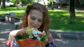 Mujer hermosa joven que admira un ramo de flores almacen de video