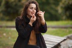 Mujer hermosa joven que aplica el lápiz labial al aire libre Juventud, estilo, Imágenes de archivo libres de regalías
