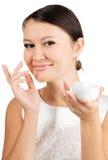 Mujer hermosa joven que aplica la crema de piel Imagen de archivo libre de regalías