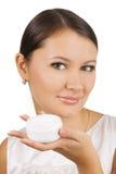 Mujer hermosa joven que aplica la crema de piel Imagenes de archivo