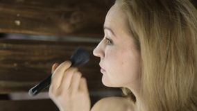 Mujer hermosa joven que aplica maquillaje delante del espejo Las sombras aplicaron con el cepillo grande en mejillas almacen de video