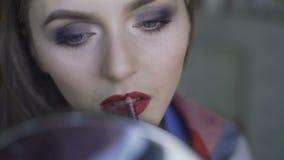 Mujer hermosa joven que aplica su lápiz labial del bordo en un espejo 4K metrajes