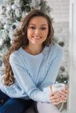 Mujer hermosa joven que bebe el café caliente que se sienta en el sofá i Fotografía de archivo libre de regalías