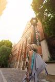 Mujer hermosa joven que camina abajo de la calle a lo largo de un edificio de ladrillo viejo contra la perspectiva de luz del sol Imágenes de archivo libres de regalías