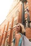 Mujer hermosa joven que camina abajo de la calle a lo largo de un edificio de ladrillo viejo contra la perspectiva de luz del sol Foto de archivo