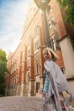 Mujer hermosa joven que camina abajo de la calle a lo largo de un edificio de ladrillo viejo contra la perspectiva de luz del sol Imagen de archivo