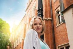 Mujer hermosa joven que camina abajo de la calle a lo largo de un edificio de ladrillo viejo contra la perspectiva de luz del sol Imagenes de archivo