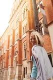 Mujer hermosa joven que camina abajo de la calle a lo largo de un edificio de ladrillo viejo contra la perspectiva de luz del sol Fotografía de archivo