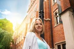 Mujer hermosa joven que camina abajo de la calle a lo largo de un edificio de ladrillo viejo contra la perspectiva de luz del sol Imagen de archivo libre de regalías