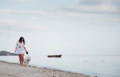 Mujer hermosa joven que camina con su perro en la playa Foto de archivo