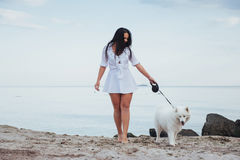 Mujer hermosa joven que camina con su perro en la playa Fotos de archivo