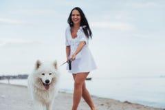 Mujer hermosa joven que camina con su perro en la playa Imagen de archivo libre de regalías