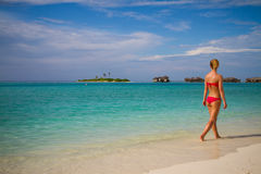 Mujer hermosa joven que camina en una playa tropical Fotos de archivo libres de regalías