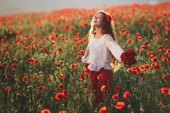 Mujer hermosa joven que camina y que baila a través de un campo de la amapola en la puesta del sol imágenes de archivo libres de regalías