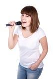 Mujer hermosa joven que canta con el micrófono aislado en blanco Foto de archivo libre de regalías
