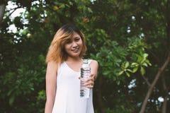 Mujer hermosa joven que celebra el agua en el parque verde Fotos de archivo