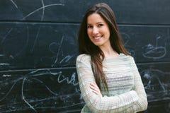 Mujer hermosa joven que coloca en frente una pared de la pizarra Fotografía de archivo libre de regalías