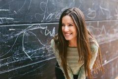 Mujer hermosa joven que coloca en frente una pared de la pizarra Fotos de archivo libres de regalías