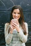 Mujer hermosa joven que coloca en frente una pared de la pizarra Imagen de archivo