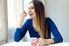 Mujer hermosa joven que come el yogur en casa Fotos de archivo