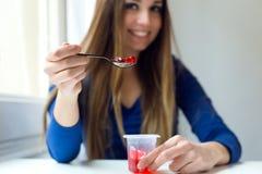 Mujer hermosa joven que come el yogur en casa Imagen de archivo