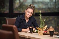 Mujer hermosa joven que come en un restaurante Imagen de archivo libre de regalías