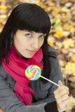 Mujer hermosa joven que come los lollipops del caramelo Fotos de archivo libres de regalías