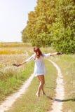 Mujer hermosa joven que corre en hierba descalzo y que sostiene los zapatos en manos Fotos de archivo libres de regalías