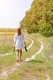 Mujer hermosa joven que corre en hierba descalzo y que sostiene los zapatos en manos Imagen de archivo
