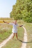 Mujer hermosa joven que corre en hierba descalzo y que sostiene los zapatos en manos Imagenes de archivo