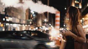 Mujer hermosa joven que cruza el centro de la ciudad del camino del tráfico adentro de Nueva York, América por la tarde y usando  metrajes