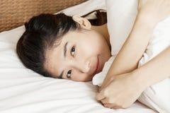 Mujer hermosa joven que duerme en cama, por mañana Foto de archivo