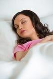 Mujer hermosa joven que duerme en la cama Foto de archivo libre de regalías