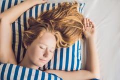 Mujer hermosa joven que duerme en su cama y que se relaja en el MES Fotografía de archivo