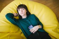 Mujer hermosa joven que duerme en una silla brillante cómoda y que sostiene un teléfono Relájese en la rotura Oficina moderna Imagenes de archivo