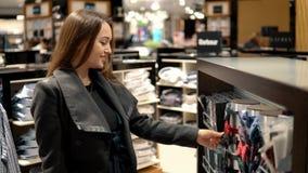 Mujer hermosa joven que encuentra un bowtie del regalo en un supermercado de la tienda almacen de video