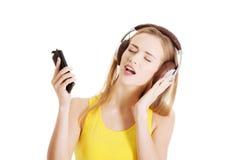 Mujer hermosa joven que escucha la música con los auriculares. Fotos de archivo