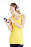 Mujer hermosa joven que escucha la música con los auriculares. Foto de archivo libre de regalías