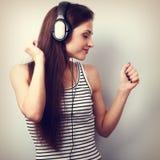 Mujer hermosa joven que escucha la música de los auriculares modernos Fotos de archivo libres de regalías