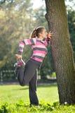Mujer hermosa joven que estira su pierna en el parque de la ciudad Foto de archivo libre de regalías