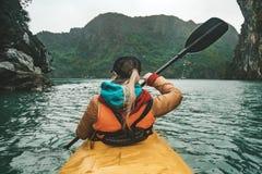 Mujer hermosa joven que flota en un kajak entre las rocas que se pegan fuera del mar La muchacha que rema los remos en el fondo d fotos de archivo libres de regalías