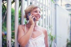 Mujer hermosa joven que habla en el teléfono móvil al aire libre Foto de archivo