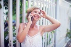 Mujer hermosa joven que habla en el teléfono móvil al aire libre Fotografía de archivo libre de regalías