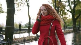 Mujer hermosa joven que habla en su teléfono móvil en un fondo Muchacha cabelluda rizada roja emocionada, feliz que camina en almacen de video