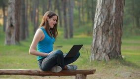 Mujer hermosa joven que habla y que trabaja usando el ordenador portátil en naturaleza almacen de metraje de vídeo