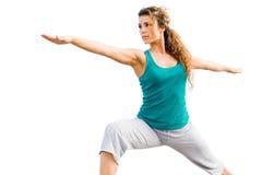 Mujer hermosa joven que hace actitud del guerrero de la yoga imagen de archivo