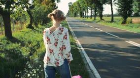 Mujer hermosa joven que hace autostop la situación en el camino con una maleta metrajes